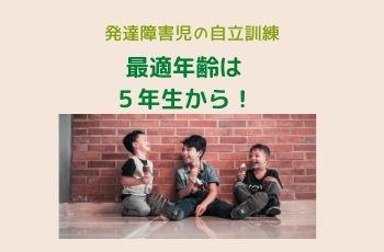 レンガの壁の前でアイスクリームを持って床に座る3人の男の子