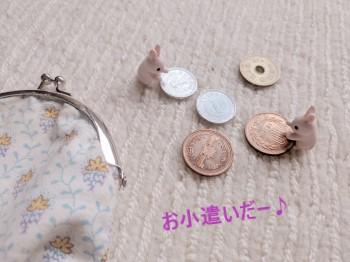 がま口財布と1、5、10円玉を持つうさぎのミニチュア
