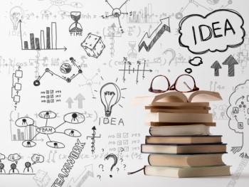 山積みの本と眼鏡とアイデアの手書きメモ
