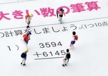 筆算のプリントと6人の小学生のミニチュア人形