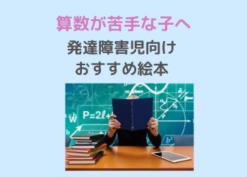 数式が書いてある黒板の前で本を読む人