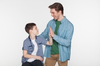 笑顔で片手タッチする父親と息子