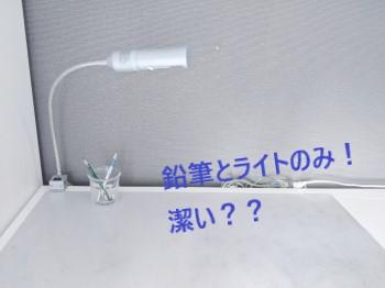銀色のライトと鉛筆立てのみのシンプルな机の上