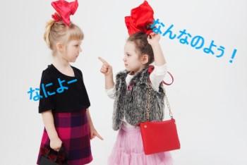 言い合いをする大きな赤いリボンをした二人の女の子