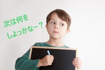 白い背景に黒いボードを抱えながら何かを考えている男の子