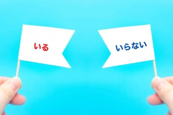 水色の背景に「いる」「いらない」と書いた旗を持つ指