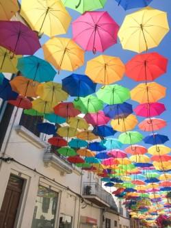 たくさんのカラフルな傘がアーケードの屋根になった外国の街の風景