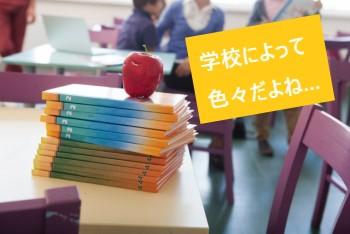 外国の学校の机に積みあげられた教科書とリンゴ