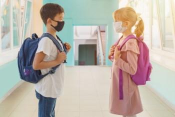 外国の学校での廊下で向かい合わせに立つマスクをした男の子と女の子
