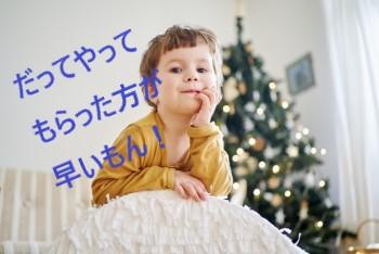 大きな白いクッションに頬杖ついて笑う男の子とクリスマスツリー