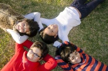 芝生に寝転んで笑う4人の子ども達