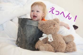 ゴミ箱に入って笑う赤ちゃんとクマのぬいぐるみ