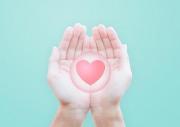 ミントグリーンの背景・開かれた両手のひらに浮かぶピンクのハート