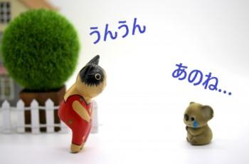 泣いているコアラとお話を聞くネコのミニチュア人形