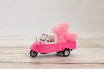 ピンクのハートを宅配するピンク色のトラックのミニチュア