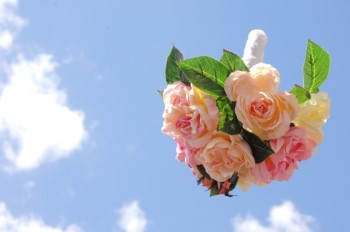 青空に投げられたバラの花束