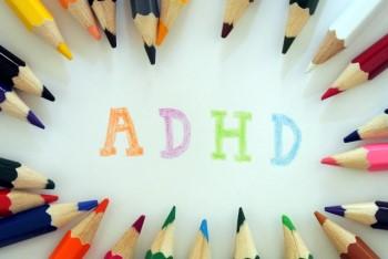 たくさんの色鉛筆に囲まれた「ADHD」という文字
