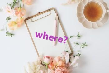 白い机に置かれたピンクの花とクリップボードと紅茶カップ