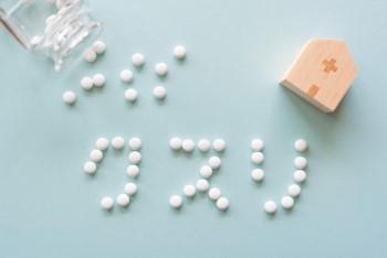 水色の背景に白い錠剤で書かれた「クスリ」の文字と家のミニチュア