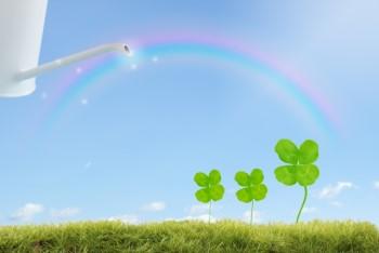 ジョウロで虹の水をかけてもらう四つ葉のクローバー