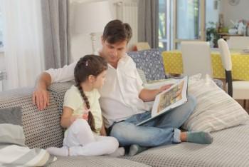 ソファーで絵本の読み聞かせをする親子