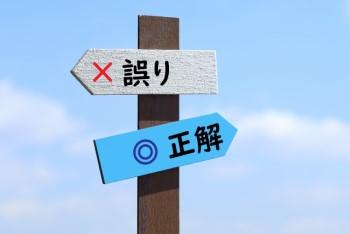 青空に「誤り」と「正解」の二つの看板