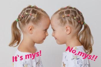 おでこをつけて見つめ合う双子の女の子