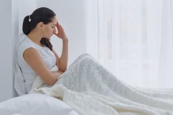 ベッドで考え込む女性