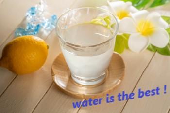 木製のテーブルに置かれたグラスの水とレモン
