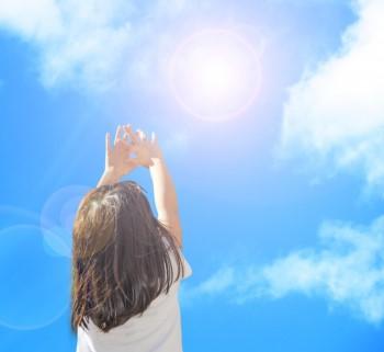 太陽に手をかざす女の子