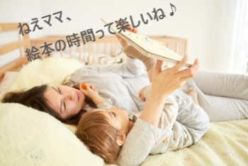 ベッドで寝ながら絵本を読む母子