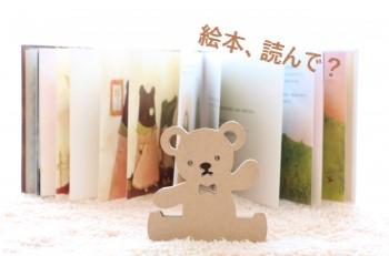 開かれた絵本と木製のクマ