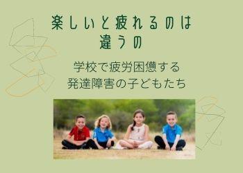 原っぱで座って笑う4人の子どもたち