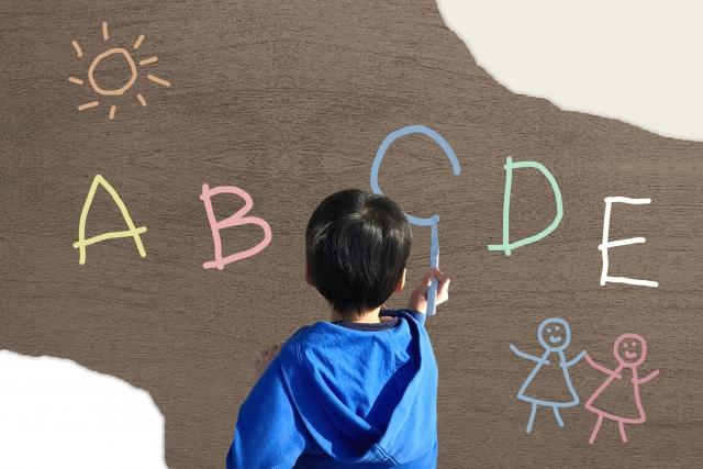 壁にアルファベットを書く男の子