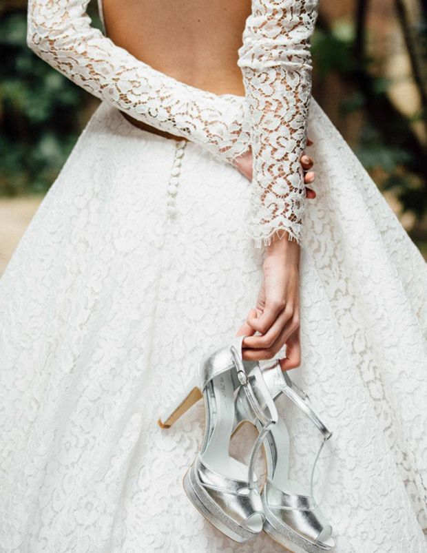 mariée tenant une paire de sandales de mariage