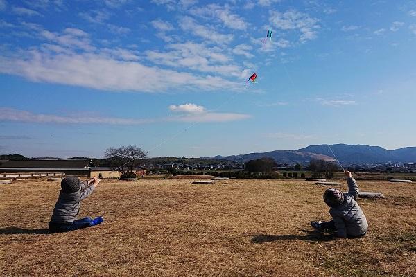 座ったまま凧揚げする子供たち