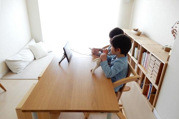 ダイニングテーブルでポータブルテレビを見る子供たち