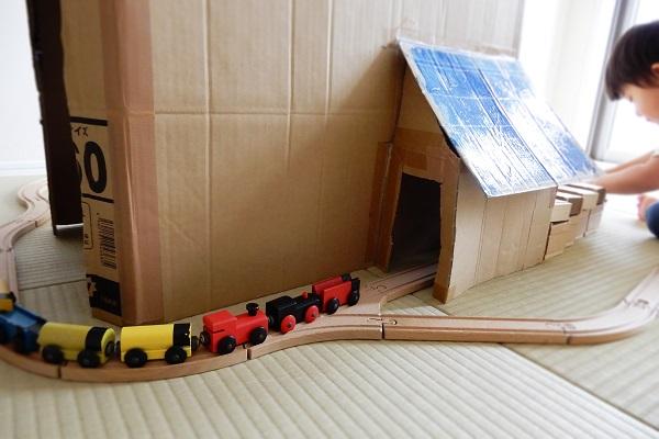 段ボールハウスを通り抜ける電車
