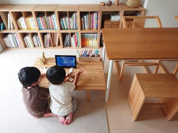 ローテーブルでポータブルテレビを見る子供たち