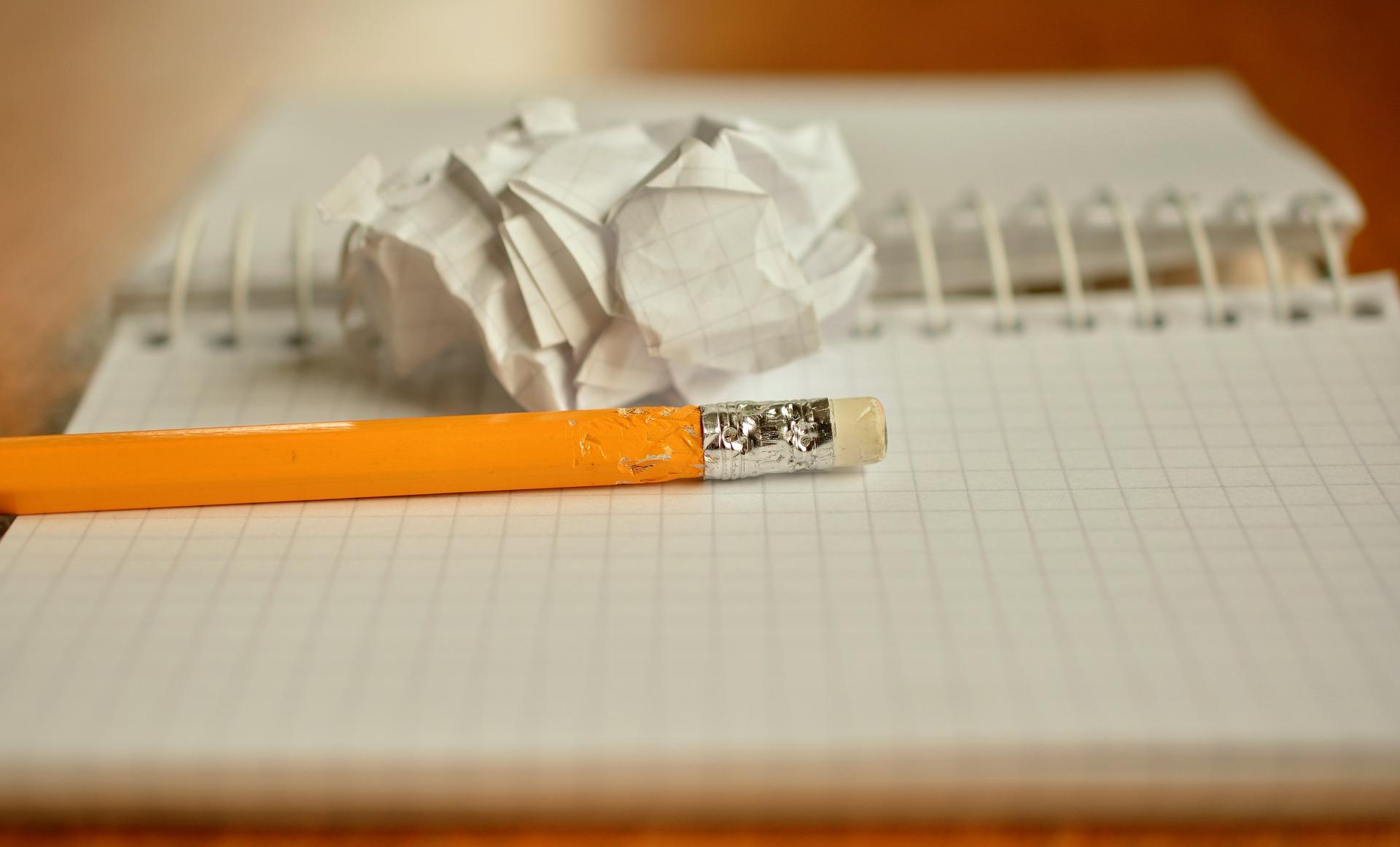 噛まれた鉛筆と丸められたメモ用紙