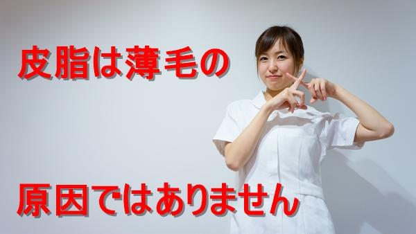 バツマークを示す若い看護師