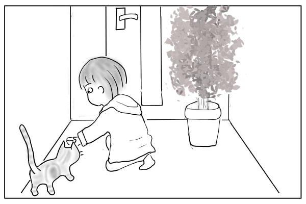 玄関で猫にえさをあげる