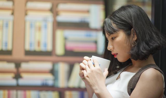 図書館でコーヒーを飲む女性の画像