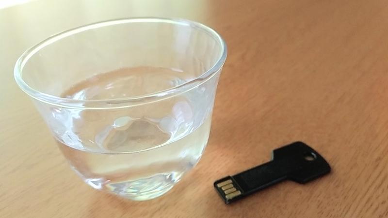 鍵の形をしたUSBメモリと水の写真