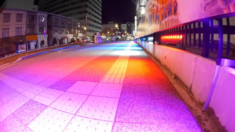 カラフルに照らされた街の歩道