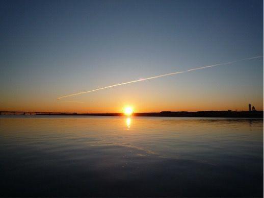 海に沈む夕日、空には飛行機雲