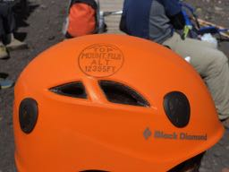 富士山頂の売店でスタンプをヘルメットに押す