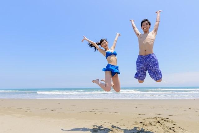 ビーチでジャンプするカップル