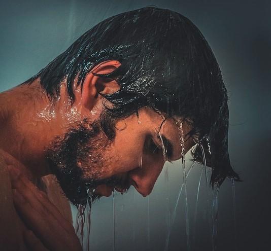 シャンプー前に素洗いをする男性