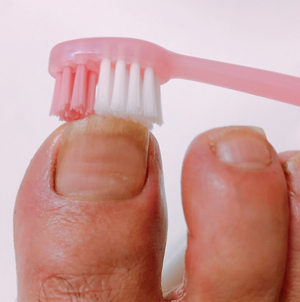 歯ブラシで足の爪垢を取っている
